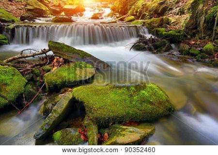 Landscape with waterfall on mountain stream