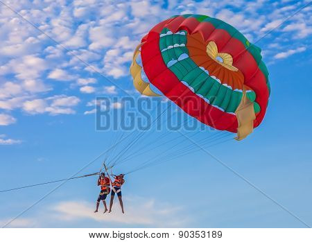 Couple Parasailing On The Beach
