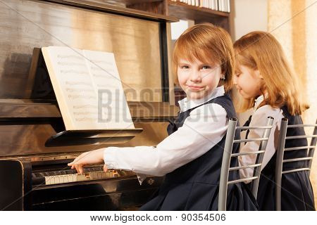 Two beautiful small girls playing piano indoors