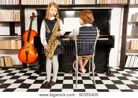 Two girls in school dresses playing on instruments