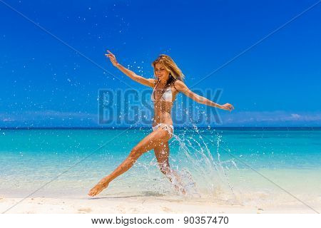 young happy woman jumping on tropical beach