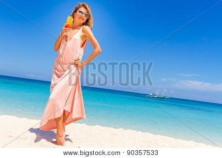 young happy beautiful woman with bright tropical cocktail on blue sky background and tropical sand beach
