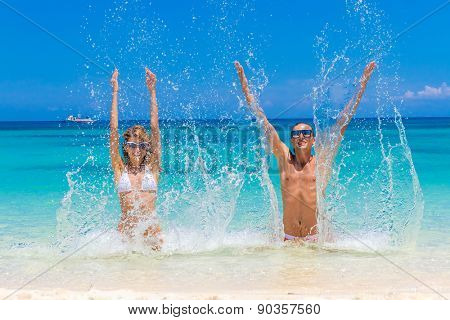 Beach couple looking. Happy young couple lying on sand under sunny summer sun. Travel holidays concept