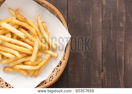 Traditional French Fries In Basket On Wooden Background