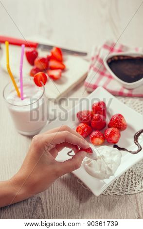 Fresh strawberries, chocolate and whipped cream on a plate. Female hand taking strawberry