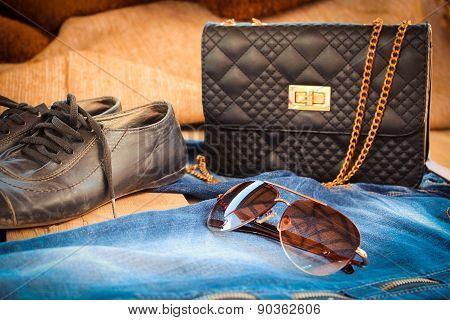 Sunglasses, jeans, handbag and shoes. Toned image.