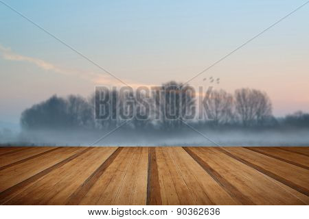 Landscape Of Lake In Mist With Sun Glow At Sunrise With Wooden Planks Floor