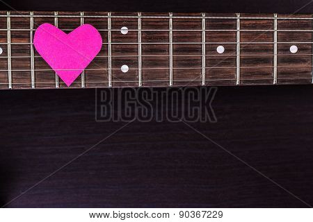 Electric guitar deck with paper heart on dark background