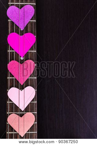 Electric guitar deck with paper hearts on dark background