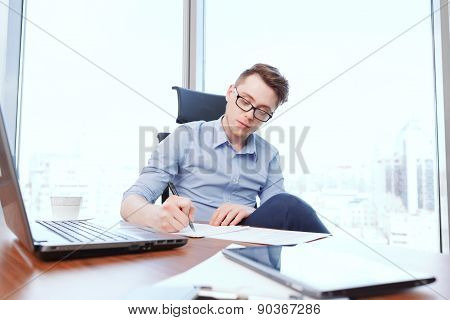 Young businessman filling papers in office