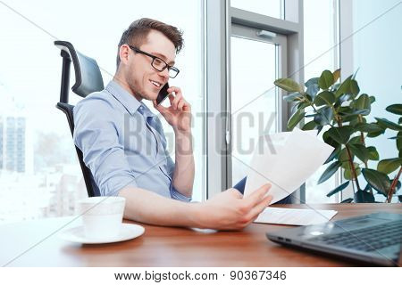 Businessman looking through papers in office