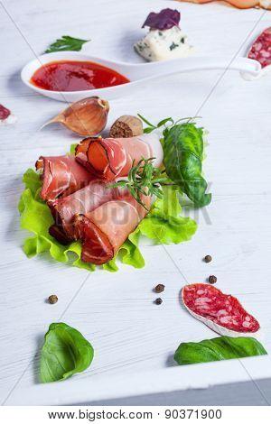 Sliced prosciutto in white wooden background