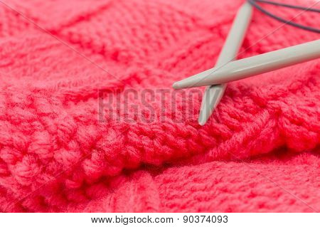 red knitted fabric, two knitting spokes close-up