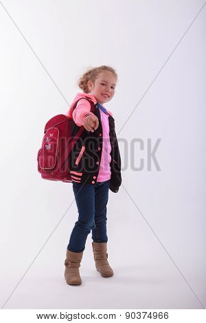 Girl with school bag points with the finger in the camera