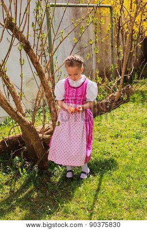 Girl in the dirndl is bored with coloured ones wobble in the hand