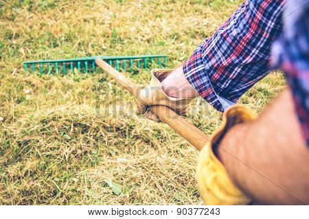 Man arms raking hay with pitchfork on field