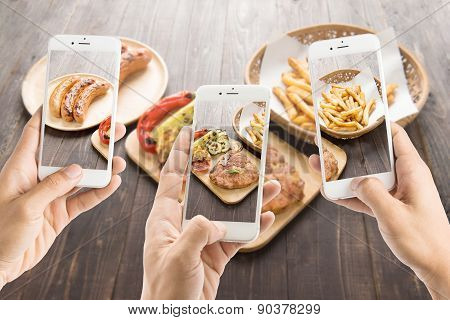 Friends Using Smartphones To Take Photos Of Sausage And Pork Chop And French Fries
