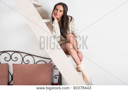 Amazingly beautiful brunette charming woman in white sweater is sitting at the stairs home.