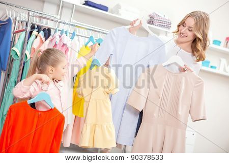 Mother and her daughter holding hangers with colorful dresses
