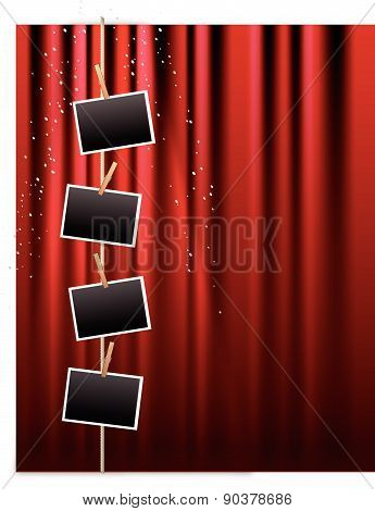 Blank photo frames hanging from a clothes line on a red curtain
