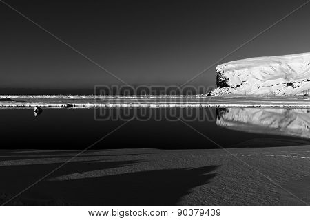 Low key black & white image, ice cliffs and reflection on lake at Skaftafell, Iceland.