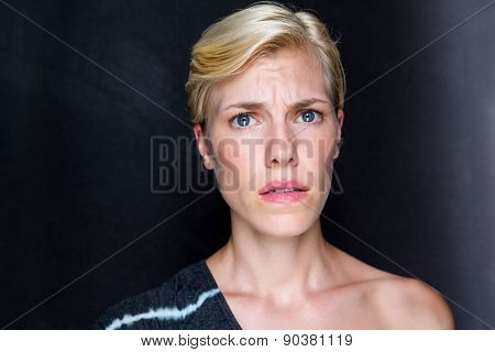 Anxious blonde woman looking at camera on black background