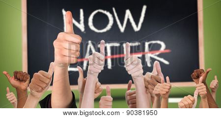 Hands showing thumbs up against now and later written on blackboard