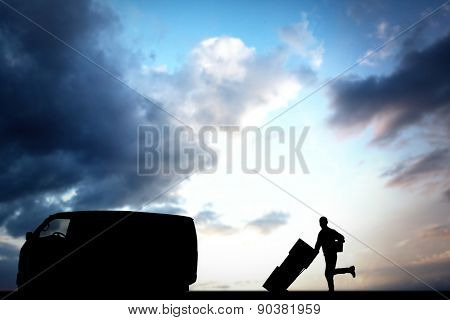 Happy delivery man with trolley of boxes running on white background against cloudy sky