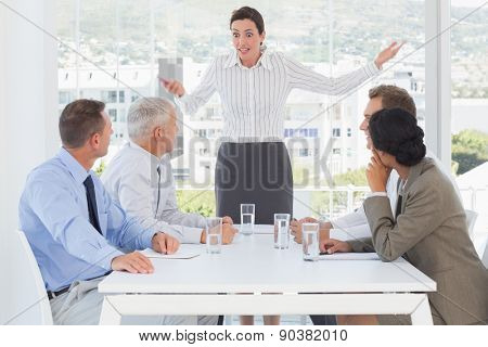 Irritated businesswoman talking to her colleagues in the office