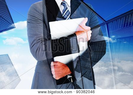 Businessman holding his laptop tightly against skyscraper