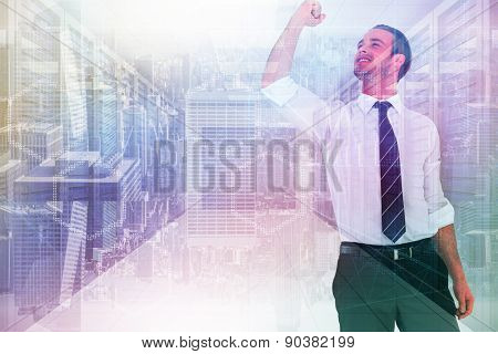 Businessman cheering with clenched fist against server room with towers
