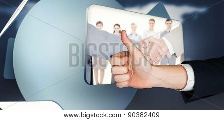 Hand showing thumbs up against screen displaying handshake and business people in digital inter