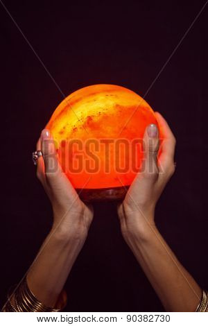 Fortune teller holding crystal ball on black background