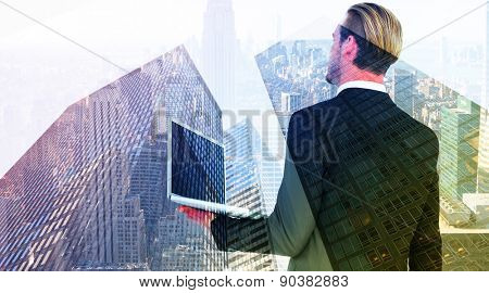 Businessman looking up holding laptop against skyscraper