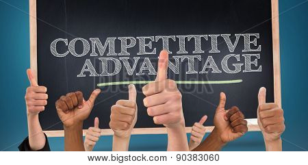 Hands showing thumbs up against competitive advantage written on a chalkboard