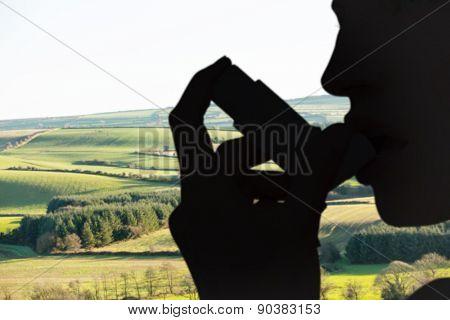 Blonde woman taking her inhaler against scenic landscape