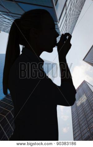 Beautiful blonde using an asthma inhaler against skyscraper