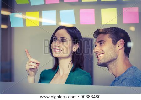 Colleagues looking at sticky notes in creative office