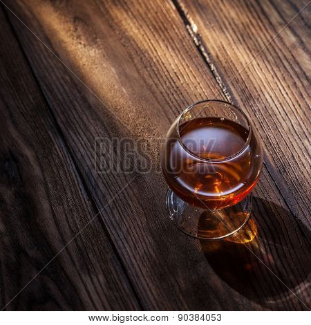 Cognac in glass on the wooden surface