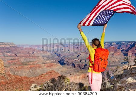 Woman with rucksack holding American flag, USA