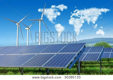 solar panels and wind turbines under blue sky with world map made of clouds