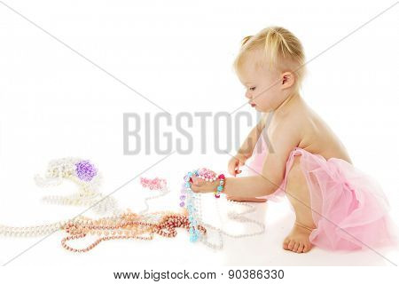 An adorable little girl squatting as she picks up a fistful of colorful pearls.  On a white background with plenty of space for your text above the multiple necklaces on the floor.