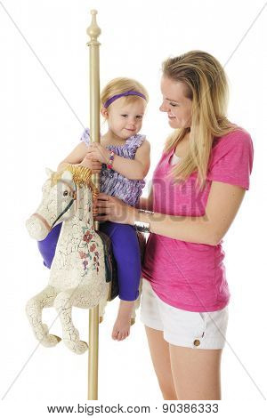 An adorable 2-year-old happily riding an antiqued carousel horse with her mommy by her side.  On a white background.