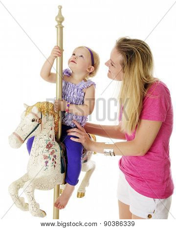 An adorable 2-year-old looking up as she rides a a flowery carousel horse, her mother by her side.  On a white background.  Focus on mother's eye.