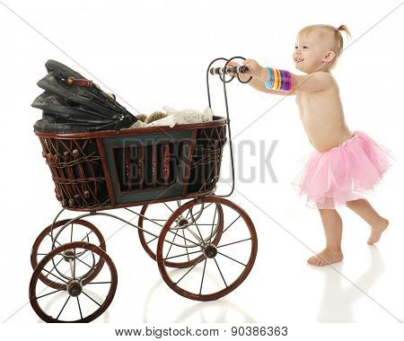 An adorable barefoot 2-year-old delightedly pushing an old buggy with her toy bear.  On a white background.
