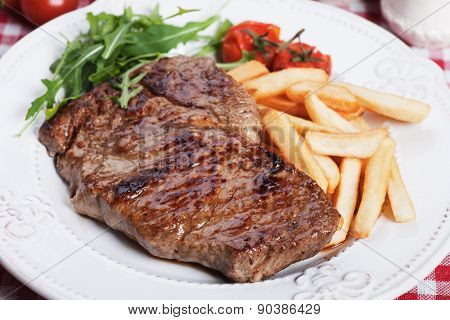 Beef rib-eye steak with french fries and rocket salad