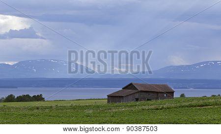 Sun-rays over meadows, barn, lake and mountains.