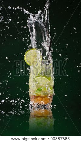 Fresh mojito drink with ice cubes and splashes on black background