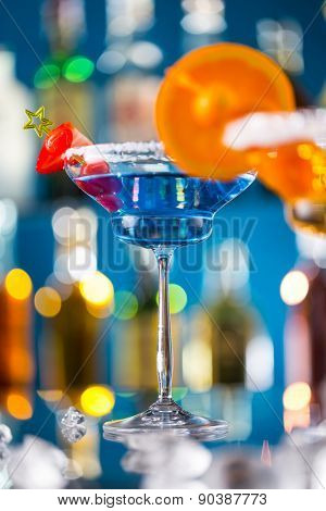 Martini drink served on bar counter with blur bottles on background
