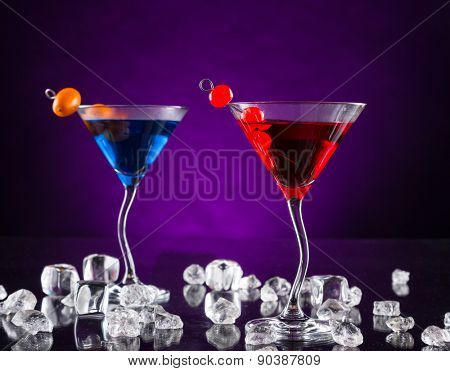 Martini drinks served on glass table with colored dark background